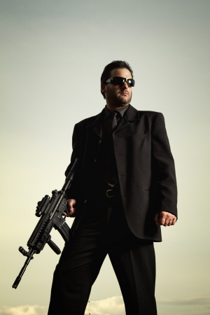 View of a contracted type killer agent wandering with a jacket and machine gun. Stock Photo - 17496079