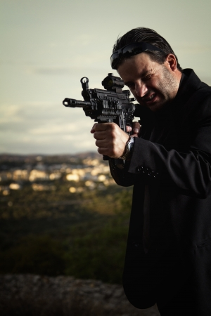 View of a contracted type killer agent wandering with a long jacket and machine gun. photo