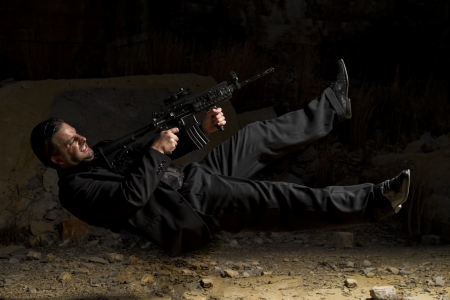 contracted: View of a contracted type killer agent in middle air with a machine gun. Stock Photo