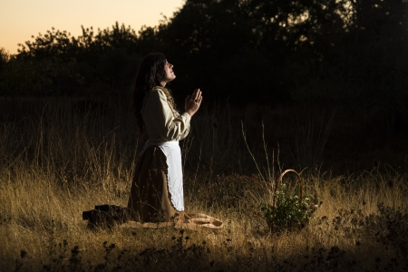women praying: View of a beautiful girl in classic dress praying on the countryside. Stock Photo