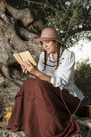 View of a beautiful girl in a classic dress in a countryside set in the shade of a very old olive tree reading a book. photo