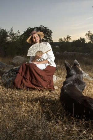 View of a beautiful girl in a classic dress in a countryside set with a dog. photo