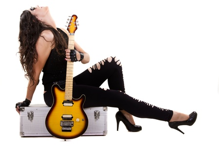 View of a beautiful girl in dark leather clothes against a white background holding an electric guitar. Stock Photo