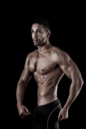 View of a muscled man on a black background in artistic, fitness and bodybuilding poses. Stock Photo - 17488827