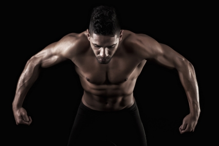 View of a muscled man on a black background in artistic, fitness and bodybuilding poses. Stock Photo - 17488627