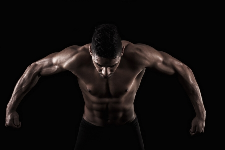 muscled: View of a muscled man on a black background in artistic, fitness and bodybuilding poses. Stock Photo