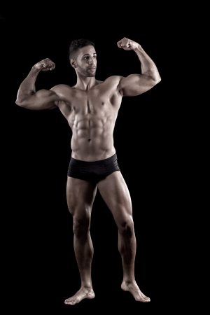 View of a muscled man on a black background in artistic, fitness and bodybuilding poses. Stock Photo - 17488413