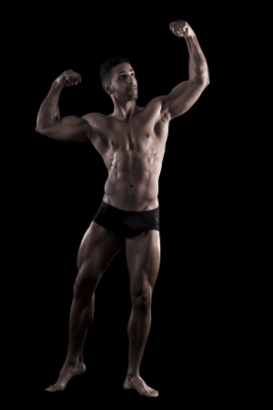 View of a muscled man on a black background in artistic, fitness and bodybuilding poses. Stock Photo - 17488380