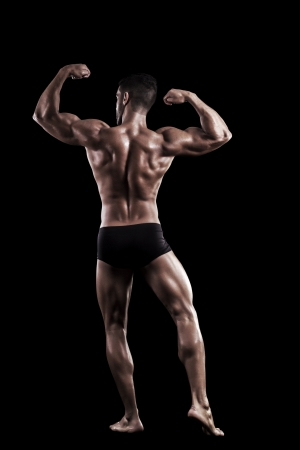 View of a muscled man on a black background in artistic, fitness and bodybuilding poses. Stock Photo - 17488390