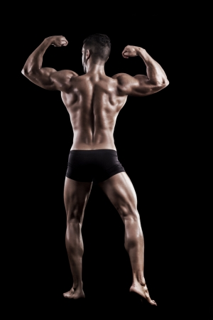 View of a muscled man on a black background in artistic, fitness and bodybuilding poses. Stock Photo - 17488402