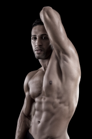 six pack abs: View of a muscled man on a black background in artistic, fitness and bodybuilding poses. Stock Photo