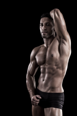 physique: View of a muscled man on a black background in artistic, fitness and bodybuilding poses. Stock Photo