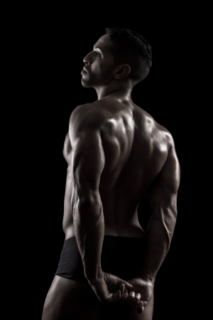 View of a muscled man on a black background in artistic, fitness and bodybuilding poses. Stock Photo - 17488838