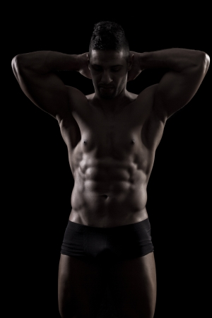 View of a muscled man on a black background in artistic, fitness and bodybuilding poses. Stock Photo - 17488924
