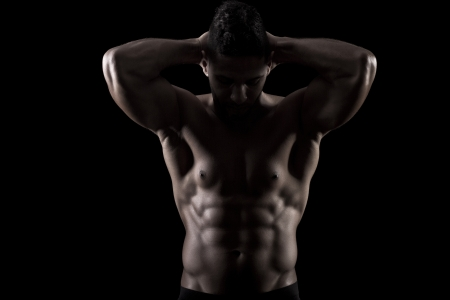 six pack: View of a muscled man on a black background in artistic, fitness and bodybuilding poses. Stock Photo