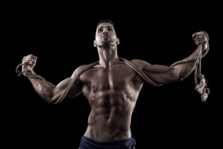 View of a muscled man on a black background in artistic, fitness and bodybuilding poses. Stock Photo