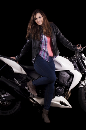 View of a beautiful young girl next to a white motorbike in a studio environment. Stock Photo - 17488817