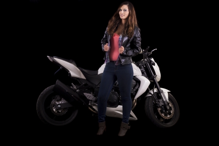 View of a beautiful young girl next to a white motorbike in a studio environment.  Stock Photo - 17488414