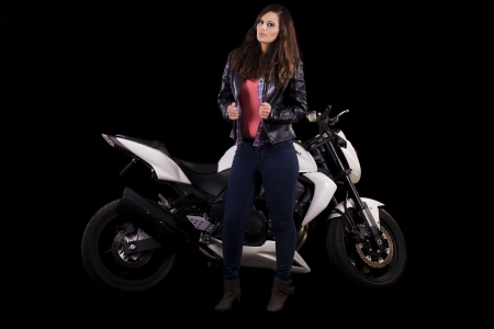View of a beautiful young girl next to a white motorbike in a studio environment. Stock Photo - 17488401