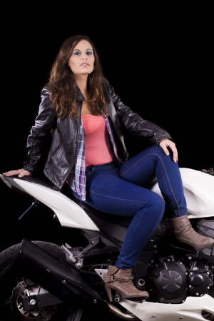 View of a beautiful young girl next to a white motorbike in a studio environment.  Stock Photo - 17489060