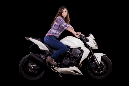 View of a beautiful young girl next to a white motorbike in a studio environment.  Stock Photo - 17488433