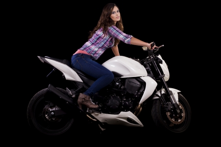 View of a beautiful young girl next to a white motorbike in a studio environment.  Stock Photo - 17488436