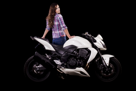 View of a beautiful young girl next to a white motorbike in a studio environment. Stock Photo - 17488439