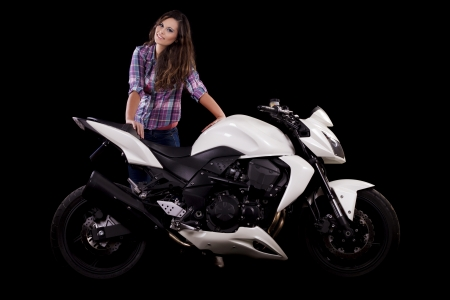 View of a beautiful young girl next to a white motorbike in a studio environment. Stock Photo - 17488464