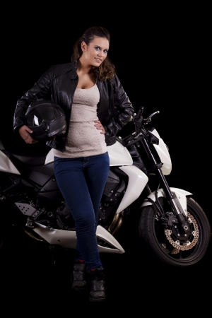 View of a beautiful young girl next to a white motorbike in a studio environment.  Stock Photo - 17488597