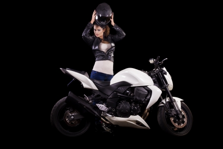 View of a beautiful young girl next to a white motorbike in a studio environment.  Stock Photo - 17488412