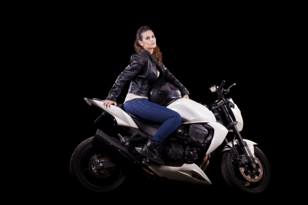 View of a beautiful young girl next to a white motorbike in a studio environment.  Stock Photo - 17488410