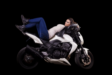 View of a beautiful young girl next to a white motorbike in a studio environment.  Stock Photo - 17488505