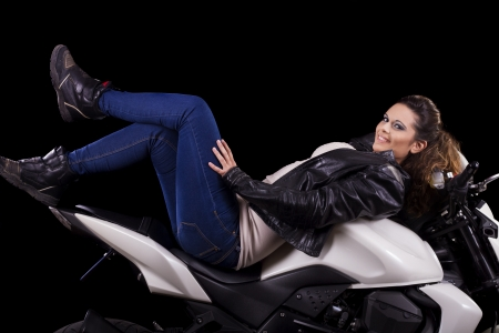 View of a beautiful young girl next to a white motorbike in a studio environment.  Stock Photo - 17488901