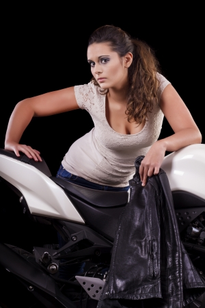 View of a beautiful young girl next to a white motorbike in a studio environment.  photo