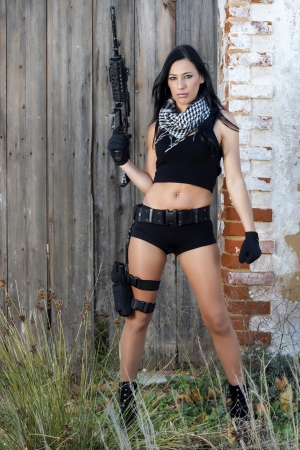View of a beautiful action girl holding a weapon in a outdoor location. Stock Photo - 17489358