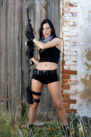 View of a beautiful action girl holding a weapon in a outdoor location. Stock Photo - 17489355