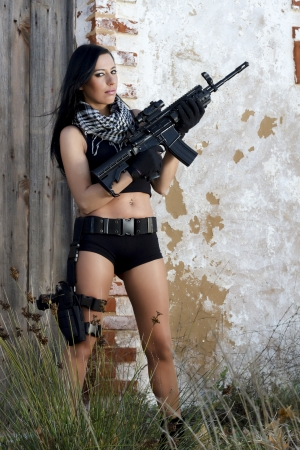View of a beautiful action girl holding a weapon in a outdoor location. Stock Photo - 17489306