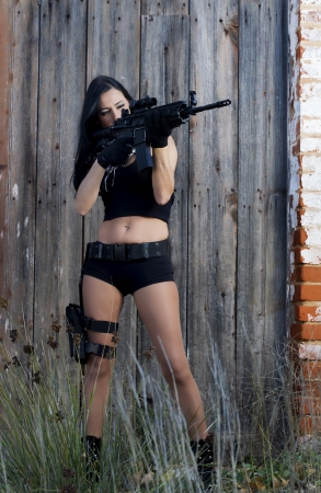 View of a beautiful action girl holding a weapon in a outdoor location. Stock Photo - 17489334