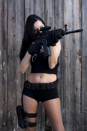 View of a beautiful action girl holding a weapon in a outdoor location. photo