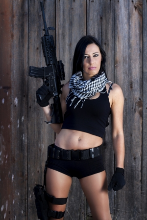 View of a beautiful action girl holding a weapon in a outdoor location. Stock Photo - 17489260