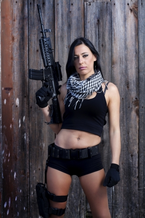 View of a beautiful action girl holding a weapon in a outdoor location. Stock Photo - 17489363