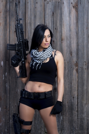 View of a beautiful action girl holding a weapon in a outdoor location. Stock Photo - 17489294
