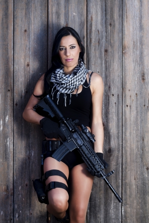 View of a beautiful action girl holding a weapon in a outdoor location. Stock Photo - 17489362