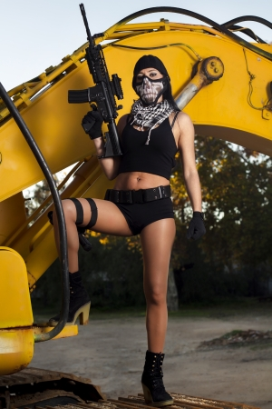 View of a beautiful action girl holding a weapon and mask, in a outdoor location. photo