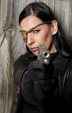 Blick auf einen schönen Aktion Mädchen mit einer Waffe in einem Outdoor-Location.