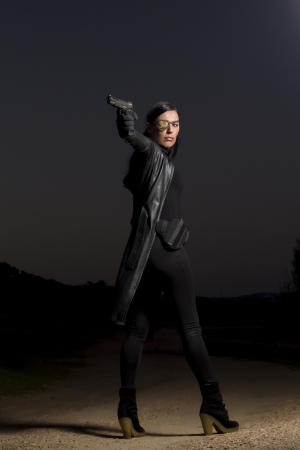 View of a beautiful action girl holding a weapon in a outdoor location. Stock Photo - 17489229