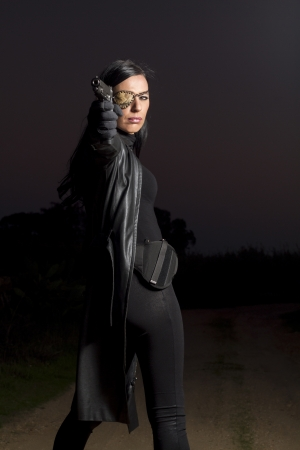 View of a beautiful action girl holding a weapon in a outdoor location. Stock Photo - 17489281