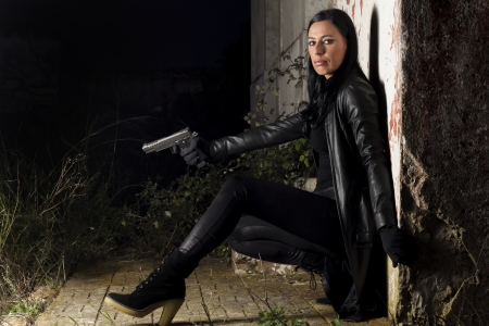 View of a beautiful action girl holding a weapon in a outdoor location. Stock Photo - 17489385