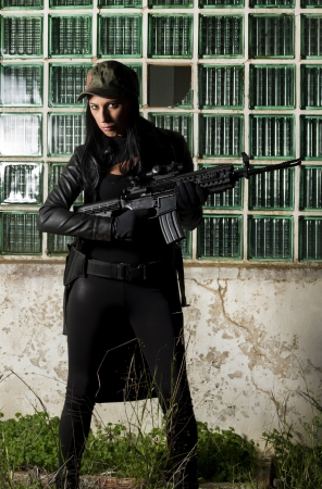 View of a beautiful action girl holding a weapon in a outdoor location. Stock Photo - 17489378