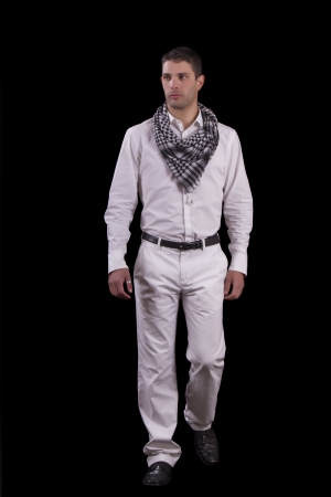 average guy: View of a young urban styled fashioned man walking isolated on a black background. Stock Photo
